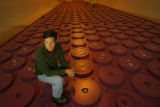 DM0758  Facility manager Ted Borst kneels atop the shield plugs that cover the containers filled...