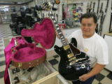 "Salesman Tony Cantu holds a replica of B.B. Kings guitar ""Lucille"" for $1199.95 at..."
