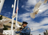 Public Safety Cadet Albert Gutierrez (cq) releases doves Friday during the Denver Police...