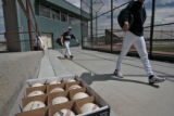 A box of baseballs waits on a bench as players from Air Academy arrive for their game against...