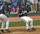 Air Academy James Doyle celebrates after sliding in safe to at home for the winning run in the...