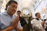 Al Coriz (cq) takes part in prayer, as just-installed Catholic Archdiocese Bishop James Conley...