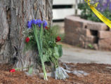 Flowers lay on the front yard as Fort Collins police and Poudre Fire Authority investigators are...