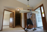 MJM1110  Jeremy Kennis (cq) carries out damaged carpet out of his family's tornado damaged home on...