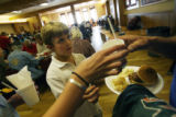 MJM041 Kent Denver school 6th grader, Nick Johnston (cq), 11, hands a free lunch to a man as the...
