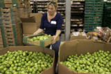 Faith Leach (cq), from Jubilee Fellowship Church in Lone Tree, prepares to load a box of green...