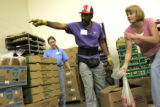 Ron Jones (cq), a volunteer at the Food Bank of the Rockies, shows Jana Schuttler (cq), from...