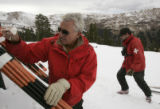 Ron Kidder, of the Loveland Ski Patrol puts down bamboo poles at the top of the lift while...