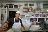 Tony Lonardo weighs some sausage for a customer at the counter Carbone's Sausage Market and Deli...