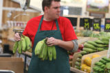 Produce clerk Arric Paul (cq) stacks bananas at Sprouts Farmers Market in Westminster Thursday...