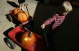 Joshua Hertzenberg (cq), 4, of Broomfield, carts away his pumpkin at the pumpkin patch while...