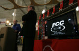 Rick Chessen Senior Legal Advisor for the FCC stands near Comm. Michael Copps and boxes of...