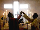 (DENVER Colo., January 2, 2005)   Father George Parathuvayalil (cq) (left) takes part in the...