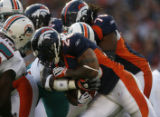 JPM195 Denver Broncos running back Michael Pittman (28) slams into  Miami Dolphins defenders in...