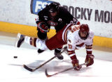 St. Cloud (Minnesota) State Husky Matt Gens (24) collides with University of Denver Pioneers left...