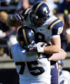 Tight end Dennis Pitta BYU jumps into the arms of teammate Scott Young after he scored a touchdown...