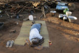 (1/17/05,Kaalapet, India)   A man sleeps on a donated mat surrounded by the few things he now has...