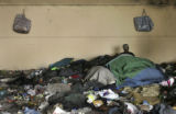 John, a homeless man, sleeps amid piles of trash underneath the Chestnut Street bridge in...