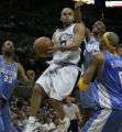 San Antonio Spurs Tony Parker, middle, splits the defense of Marcus Camby, #23, left, Wesley...