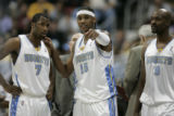 (l. to r.) Denver Nuggets Greg Buckner, Carmelo Anthony and Bryon Russell confer during a break in...