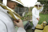 Assistant volunteer apiarist (beekeeper)Tanner Thompson,cq, 17, left, and volunteer apiarist Chris...