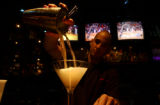 Will Sequino (cq), 26, of Littleton, Colo., pours a Dirty Kettle One martini for last call at...