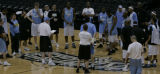 Denver Nuggets coach George Karl, left in ball cap, addresses his team before practice at the SBC...