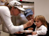 LPGA pro Kris Tschetter (cq), right, feeds her daughter, Lainey, 2, as her husband Kirk Lucas...