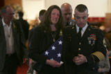 Jessica Obert, center, holds the U.S. flag as she is escorted by family friend Sgt. First Class...