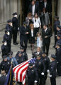 Pall bearers carry the casket of Denver Police Det. Donald Young as Young's wife, Kelly, right,...