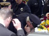 Denver Police Detective Jeff Baran kisses  Detective Donald Young's casket at the end of a...