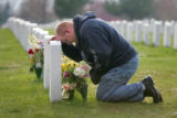 Kris Burns (cq), Laramie, Wyoming, rests on his brother Lance Corporal Kyle Burns' headstone at...