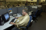 Roger Hyatt(cq), seated, (RIGHT), an ADT Home Health Security Services operator, sits at a...