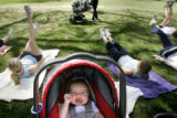 Kate Hardy, 10-weeks-old, smiles and enjoys the warm weather as her mother, Kelly Hardy, left, and...
