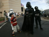 Harrison Bell, cq, 9, of Parker, aproches Darth Vader with caution while waiting in line to watch...