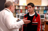 (Lt to Rt.) Denver North High School teacher Barry Bley, congratulates senior Eddie Montoya (cq)...
