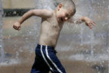 Darren Breci, 5, of Arvada, runs through the water fountains at the Promenade in Westminster,...