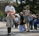 Visitors point at zookeeper Laura Ghessassi (cq) as she carries a flamingo from its winter...