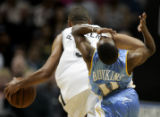 The Denver Nuggets' Earl Boykins (#11) reacts after being elbowed in the face by the San Antonio...