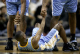 The Denver Nuggets' Earl Boykins (#11) is helped up off the floor after being fouled by the San...
