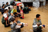XIN104 - Paramilitary police officers carry pupils out of a school hit by a flood in Shenzhen, a...