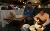 Kayia Vang, 75, right, the husband of 64-year-old Ying Yang, burns symbolic paper money as...
