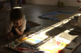 Aidan Quade,7, works on details of his painting on Monday, May 9, 2005 in the downtown Denver...