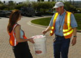 Amy Montano (cq), left, receives money from Qwest worker Brian Burke (cq), right, Tuesday morning...