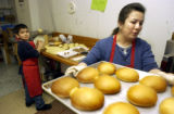 (Lamar , Colo, January 11, 2004)  Amy Gutierrez puts  reba nadas , a Mexican bread, into the oven ...