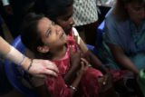(1/21/05, Samiyarpettai, India)   A little girl cries while Nancy looks at a wound on her  leg in...