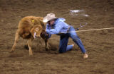 Denver, Colo., photo taken January 23, 2004- Blair Burk, of Durant, Okla., wrestles a steer to the...