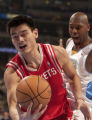 (Denver, CO., January 9, 2004) Yao Ming grabs a loose ball while being defended by Nene in the...