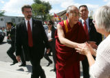 Flanked by security, the Dalai Lama shakes hands with supporters as he walks into the Newman...