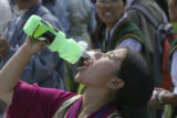 Passang Chopka, takes a drink, waiting for the arrival of the Dali Lama. She is from Tibet and is...